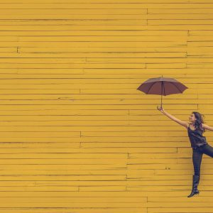 woman flyig withot wings with an umbrella against a yellow background